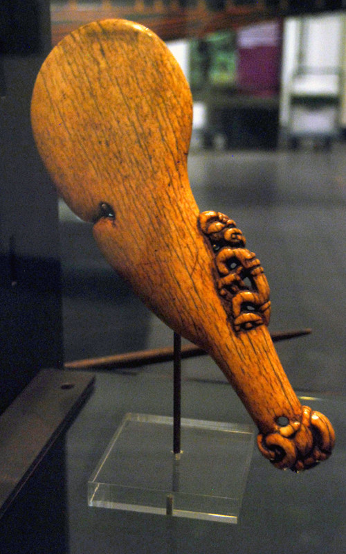 Maori bone club with figure and interrupted oval shape - a wahaika paraoa, mouth (waha) of the fish (ika) (Auckland Museum).