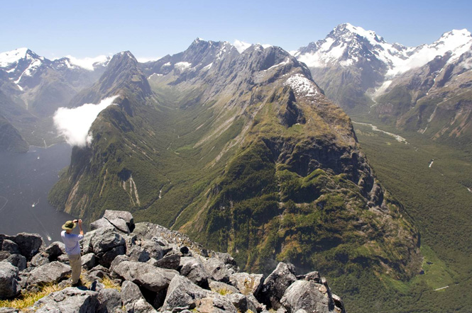 Prof Kurt Cuffey Of UC of Berkeley overlooking the glacier-carved Bowen River drainage (middle), Mount Tutoko (far right) and Milford Sound (left) in Fiordland National Park of New Zealand. (Photo by