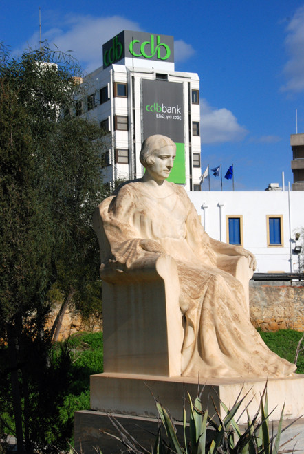 Marble sculpture of seated woman in the grounds of Agios Spyridon Church, Nicosia (with CDB Bnk in background), 2011.