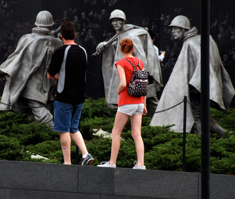 Young man and woman look at the Korean War Veterans Memorial on The National Mall, Washington D.C.