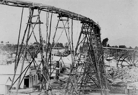 Fluming for the Great Western Company water wheel, Kaniere (1870). Note the size of the buildings. FG Hawkins., Hocken Library E3006/15.