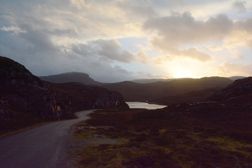 The setting winter sun and the winding sngle-track road back to Fearnmore with Loch na Creige .