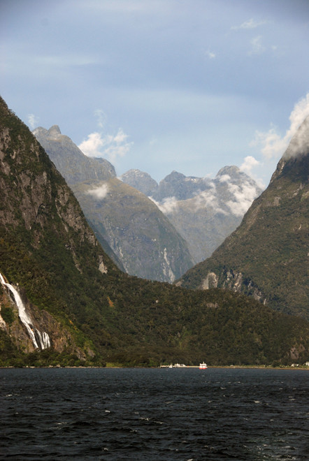 The staggering view back to the boat terminus at Milford Sound and the peaks of the Darran Mountains with their immensely steep slopes carved out of hard Plutonic rocks. Bowen Falls to the left.