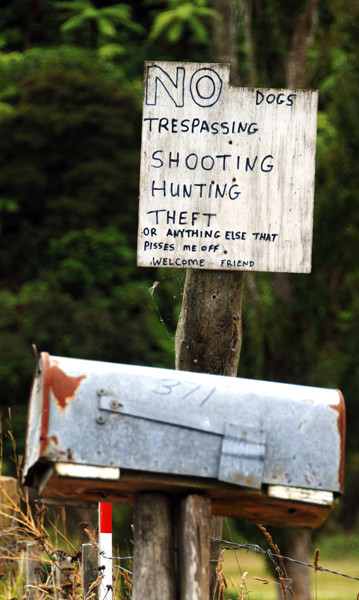 On an irregular offcut of ply above a rusty letter box someone had written, 'No dogs, trespassing, shooting, hunting, theft or anything else that pisses me off. Welcome friend.' Near Tapu on the Coromandel Peninsula.
