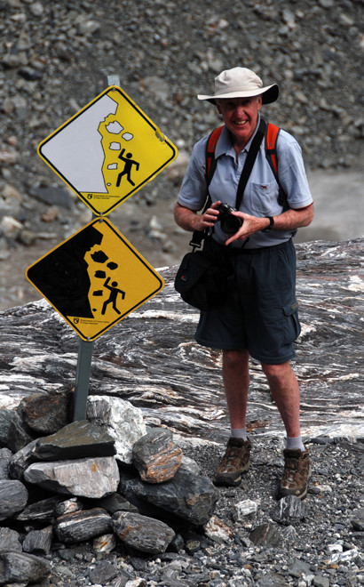 'I took a picture of him gamely standing by signs for both rock- and ice-falls.' (Fox Glacier terminus)