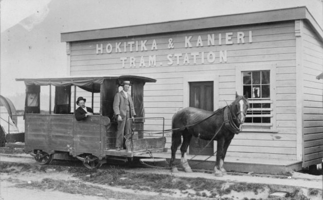 Hokitika & Kanieri tram station between 1877 and 1893. The operator Tom McGuigan sits inside and his son alongside. Ref: 1/2-018531-F. Alexander Turnbull Library, Wellington, New Zealand.