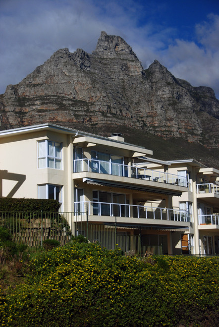White paradise: upscale housing  in Camps Bay with one of the Twelve Apostles in the background