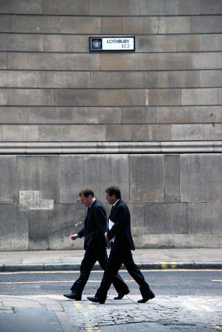 Two City men walking up Lothbury with the wall of the Bank of England in background.