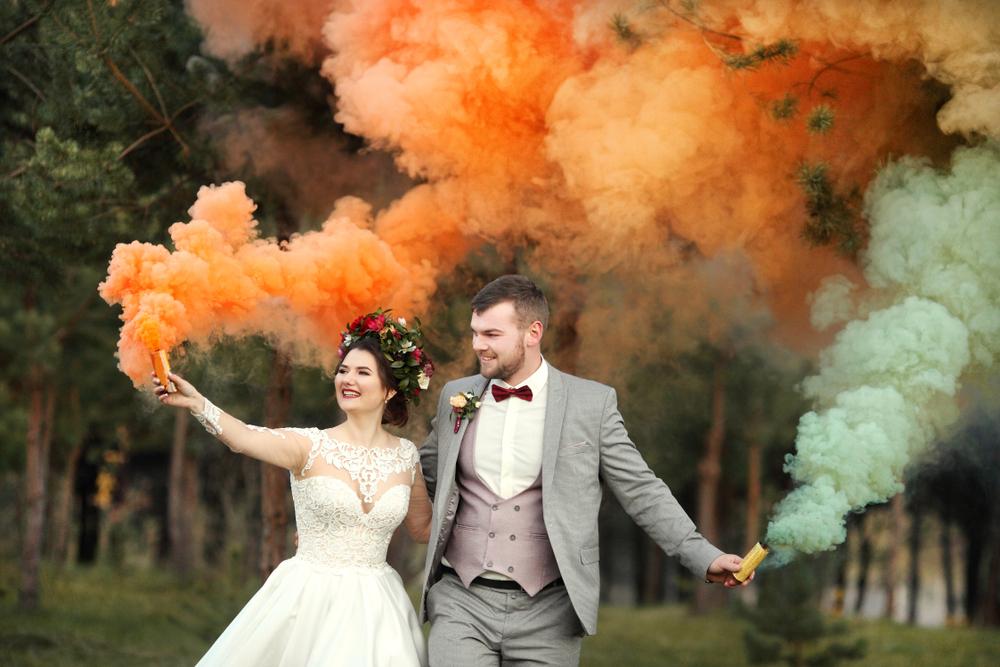 Brautpaar mit Rauchbomben bei einem Ritual mit Traurednerin während einer freien Trauung