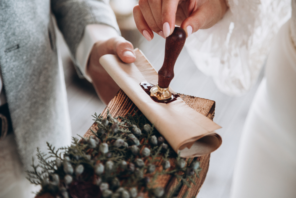Brautpaar stempelt ein Siegel auf die Urkunde einer Freien Trauung