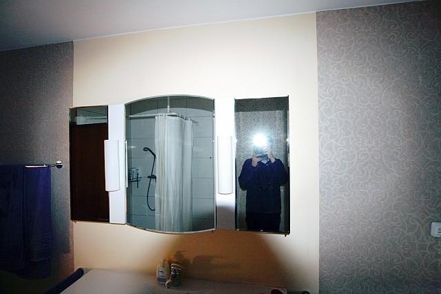 Immobilienfoto  eines Badezimmers, im Spiegel ist der Fotograf mit Blitz zu sehen.