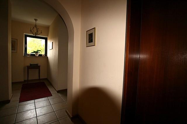 Immobilienfoto: Bild eines Flurs mit dem internen Blitz aufgehellt, Hinten wird es dunkel, ein Schatten vom Objektiv ist ebenfalls zu sehen