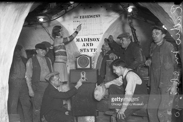 Nella foto una postazione di ascolto radio al Chicago Tunnel in State and Madison Street, durante una partita tra Cubs e Phillies - La ragazza segna il punteggio sul tabellone (Getty Images)