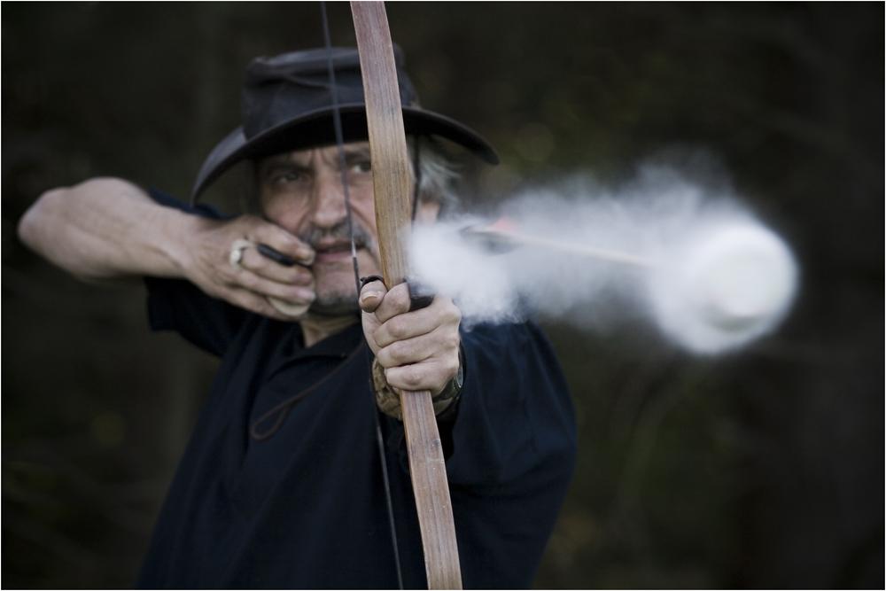 Ein Bogenschütze schießt einen mit Talkum präparierten Pfeil.