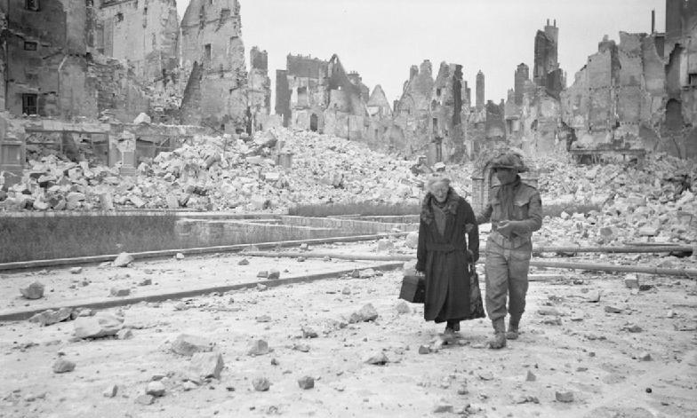 Ein britischer Soldat und eine alte Dame im zerstörten Caen in der Normandie, Sommer 1944.