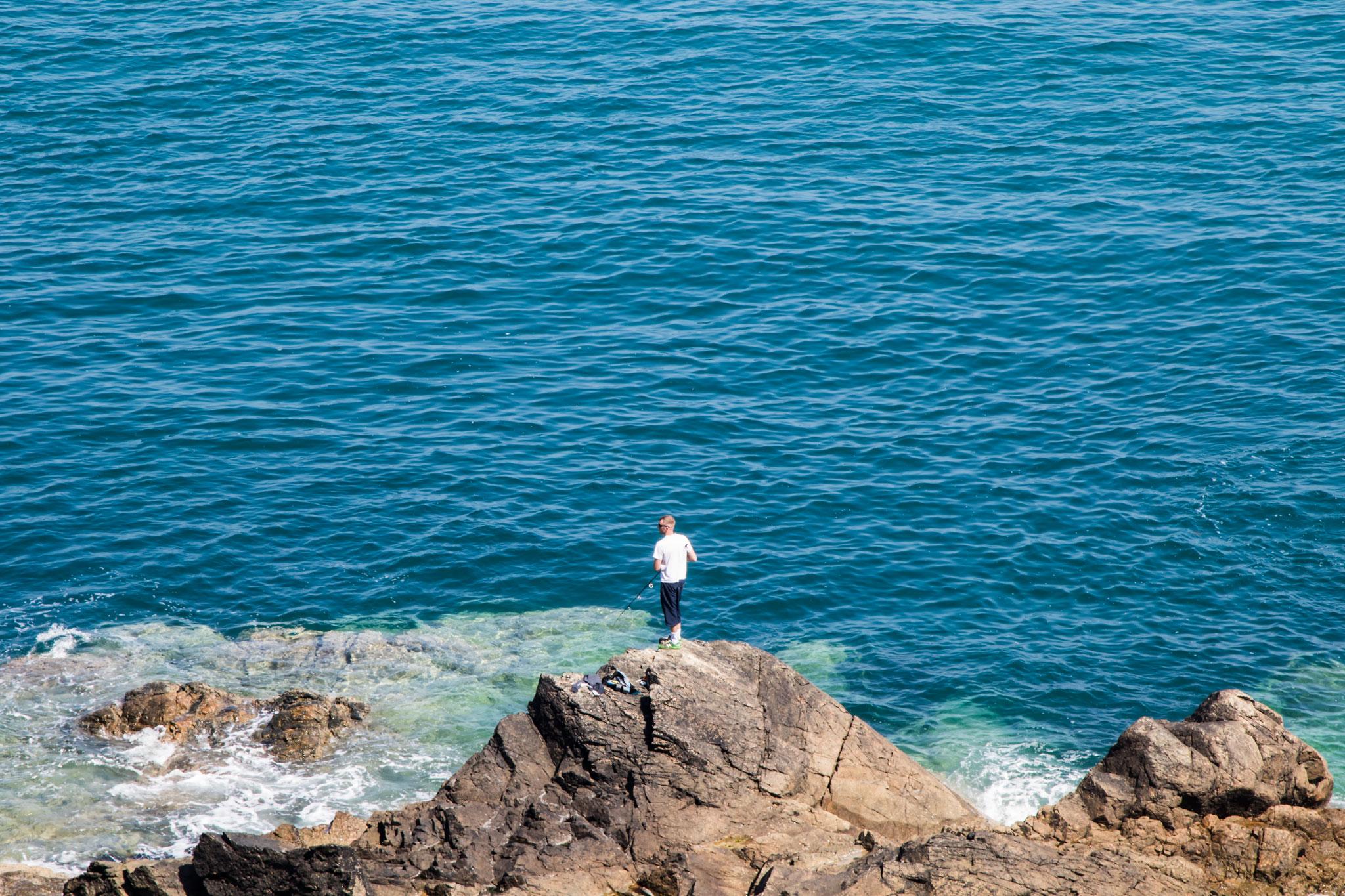Ein Mann steht an der normannischen Küste auf einem Felsen und angelt