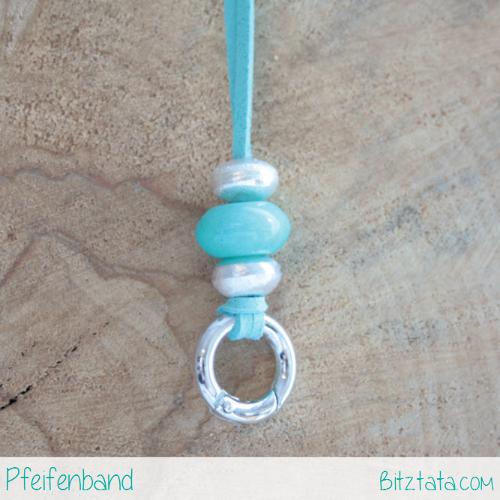 Türkises Velourimitatband mit Silberperlen und türkiser Keramikperle. Der Ring funktioniert nach dem Karabinerprinzip.