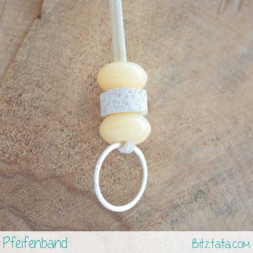 Gelbe Keramikperle kombiniert mit weißem Lavastein. Silberring zum Pfeife einhängen an cremeweißer Wachsschnur