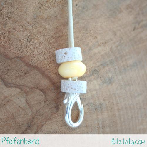 Cremeweiße Wachsschnur mit weißen Lavasteinperlen und gelber Keramikperle. Ein silberner Schnapphaken kann zum einhängen der Pfeife genutzt werden.