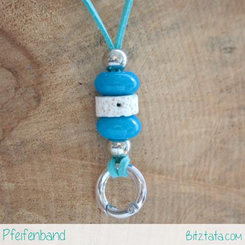 Türkises Band mit blauen Keramikperlen kombiniert mit einer weißen Lavastein- und Silberperlen. Der Ring funktioniert wie ein Karabiner und die Pfeife kann einfach eingehängt werden.