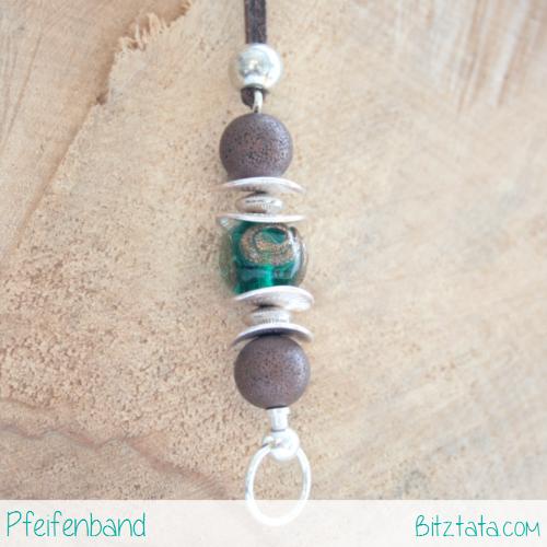 Der Wechselstab ist mit bonzierten Metallperlen, einer grünen Glasperle mit Kupferdetails kombiniert. Silberplättchen und -perlen geben Struktur. Aufgefädelt auf ein brauner Velourimitatband, gehalten mit einer zusätzlichen Silberperle.
