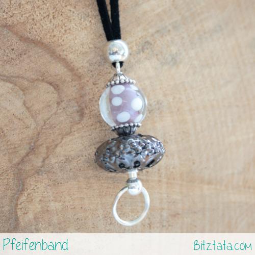 Kurzer Wechselstab mit rosa-weiß getupfter Glasperle und einer weiteren Perle in Antiksilber. Am schwarzen Velourimitatband mit einer zusätzlichen Silberperle fixiert.