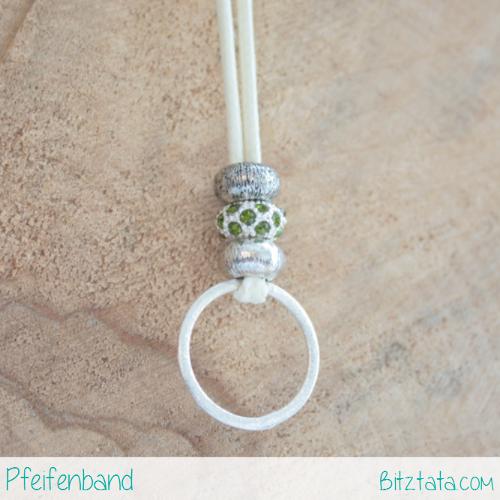 Cremeweiße Wachsschnur mit Silberperlen und grüner Strassperle. Silberring zum Pfeife einhängen.