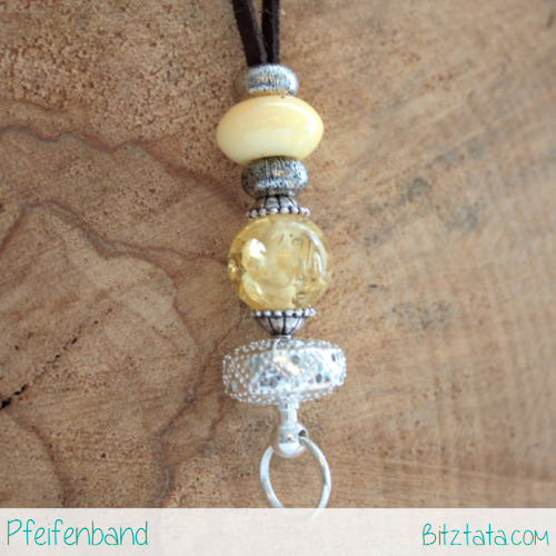 Perlenmix aus Keramik, Glas und Silber, zum Teil auf einem Wechselstab angebracht. Der untere Ring kann geöffnet werden um eine Pfeife anzubringen.