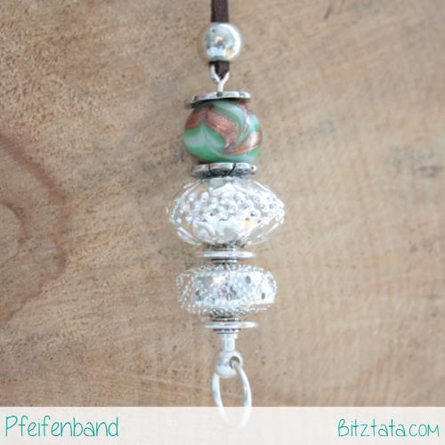 Wechselstab bestückt mit 2 verschiedenen Silberperlen und einer grünen Glasperle mit Kupferwirbeln. Weitere Silberperlen runden das Schmuckstück ab. aufgezogen auf ein brauner Velourimitatband.