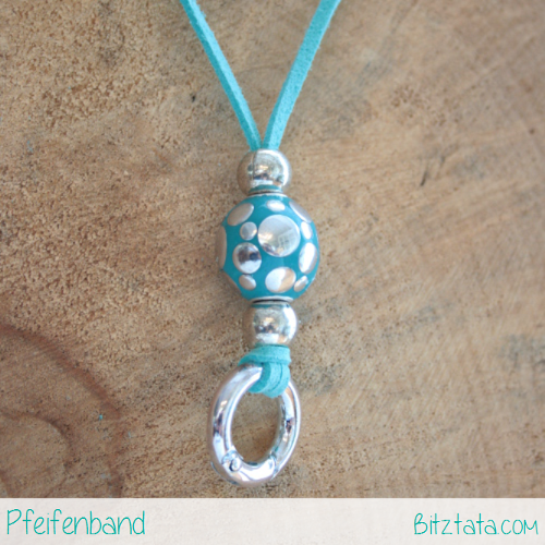 Türkises Velourimitatband mit Silberperlen und türkiser Perle mit Silberpunkten. Der Ring funktioniert nach dem Prinzip eines Karabiners zum einhängen Ihrer Pfeife.