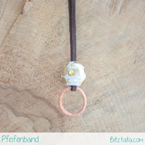 Kupferring an braunem Velourimitatband mit Weiß-goldener Perle verziert.