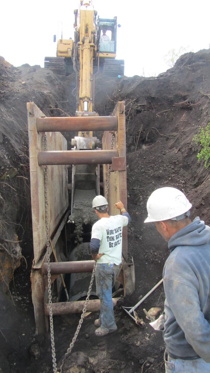 Riverfront municipal storm sewer repair with concrete encasement at 30 feet deep