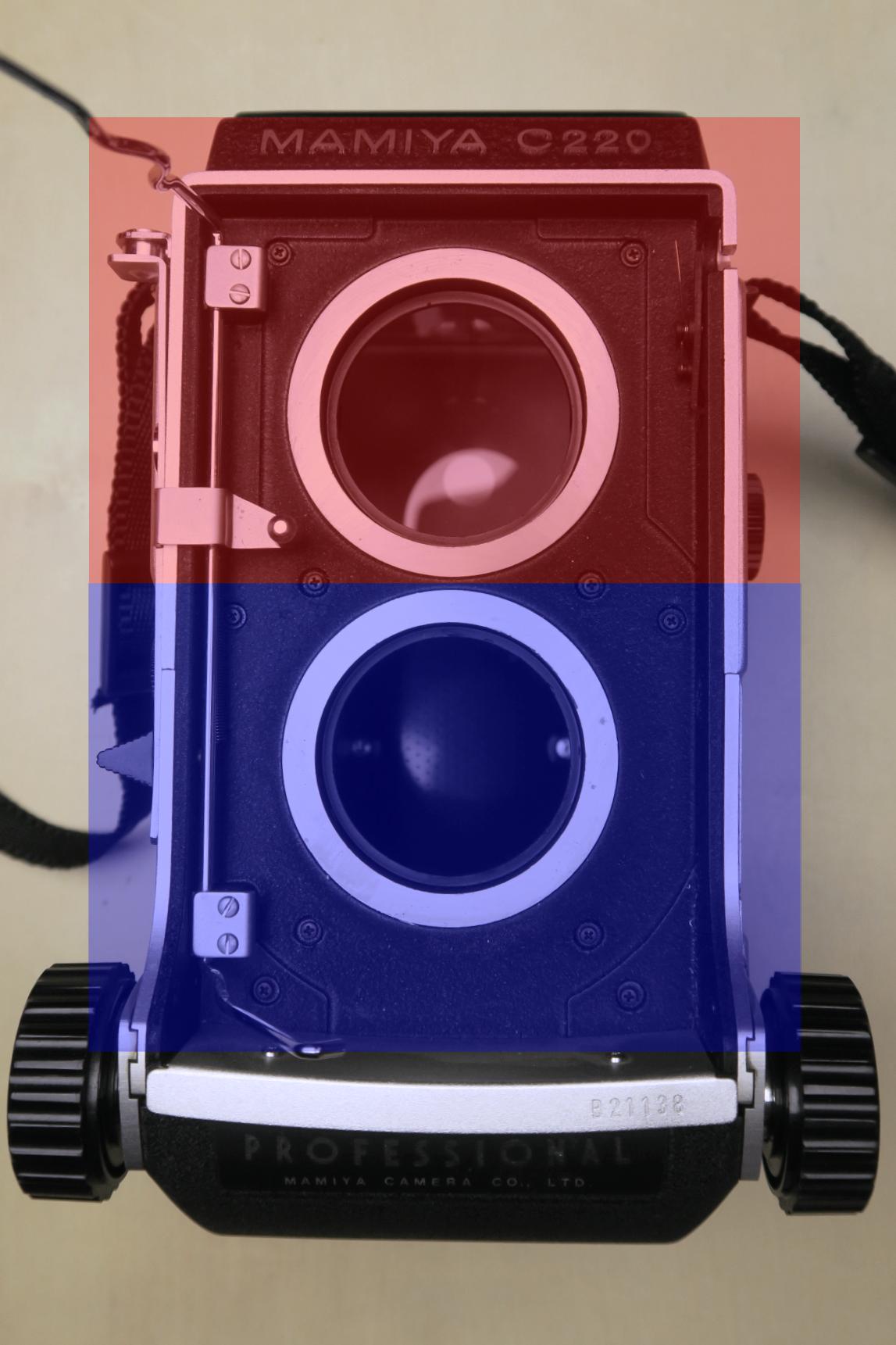 Front des zweigeteilten Kameragehäuses mit demontierter Optik. Oben: Lichtschachtsucher mit einfachem Spiegel (rot). Unten: Belichtungskorpus mit Filmrückteil (blau).
