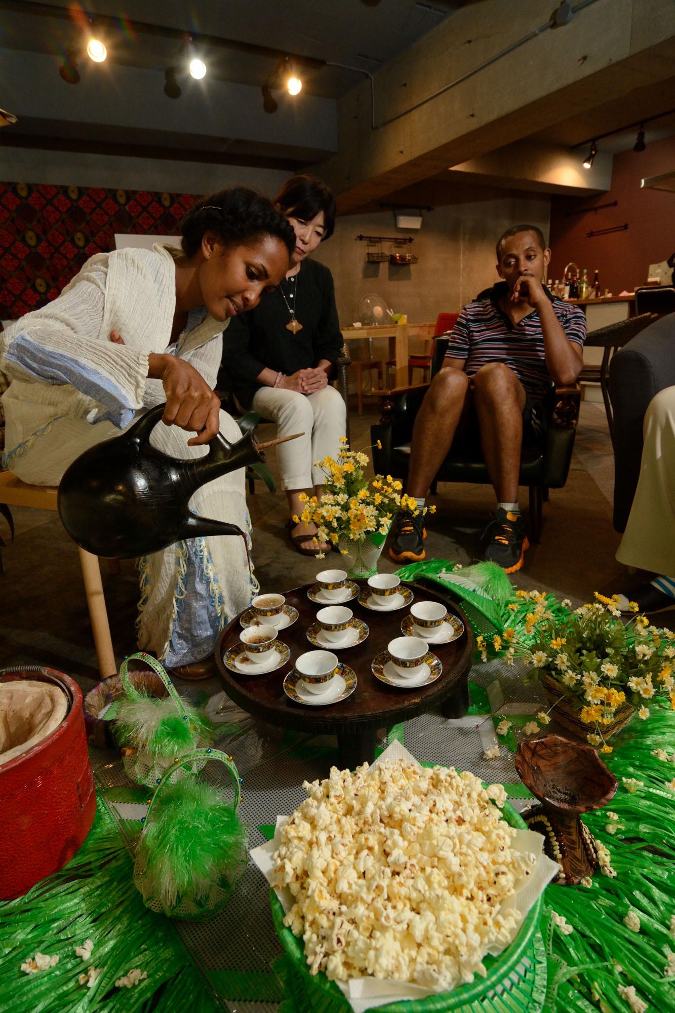 東京・八広の「油田カフェ」でエチオピアのコーヒーセレモニーを行うデンカネシさん。香を焚き、豆を煎り、3杯のコーヒーを楽しむ。ポップコーンはセレモニーでは人気のお菓子