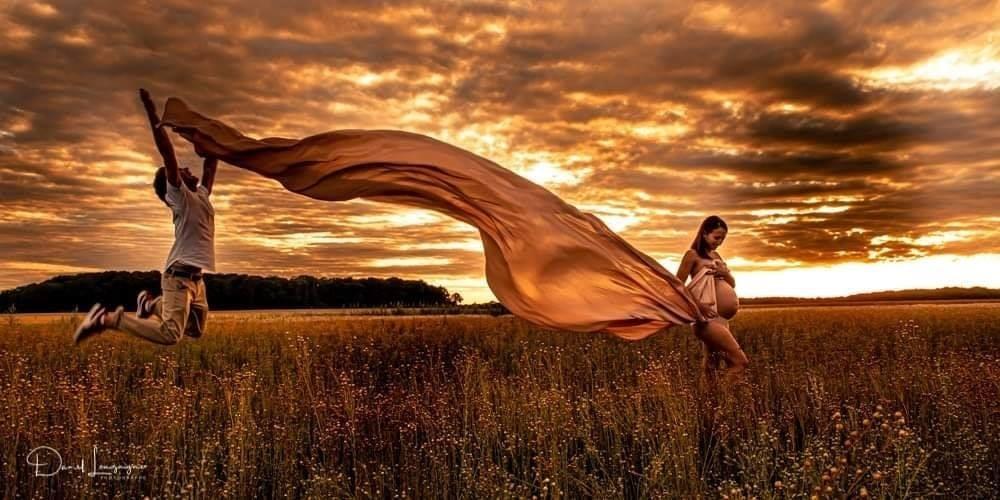 séance photo de grossesse dans les champs au coucher du soleil