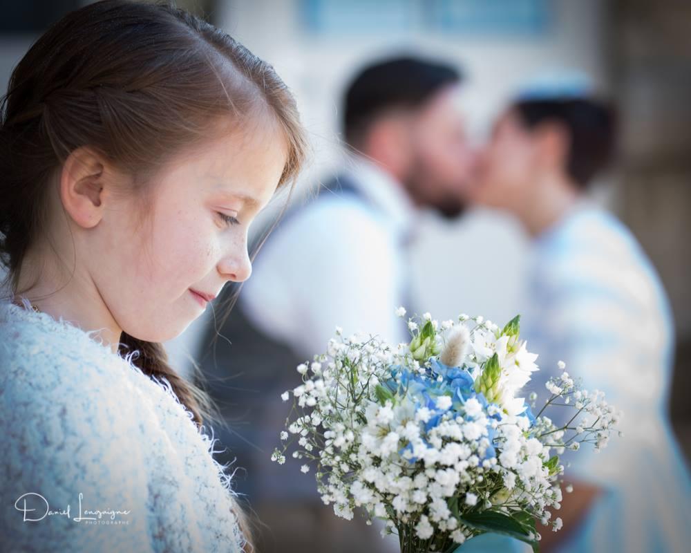 séance photo de couple de mariés; petite fille tenant le bouquet de la mariée; bisou derrière les fleurs