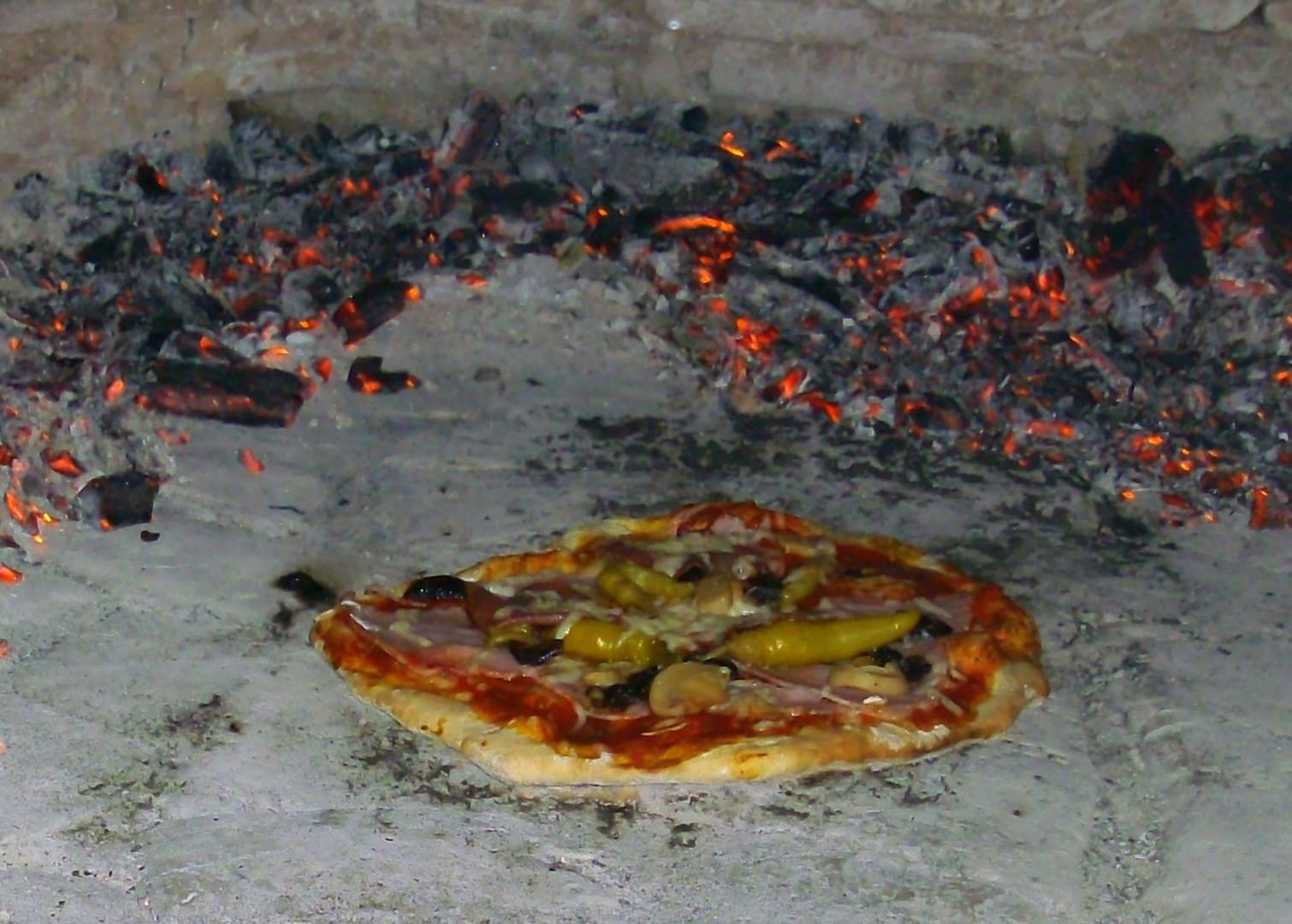 Eine der vielen leckeren Pizzen ist fast fertig!