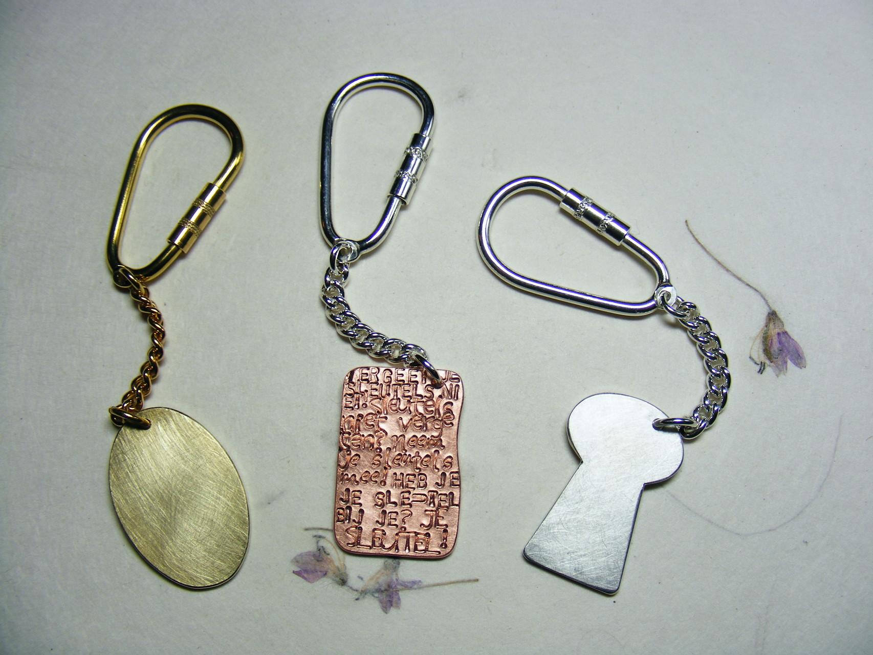 Sleutelhanger in vorm en met tekst naar keuze. Messing €15, zilver/koper €25, zilver €40.