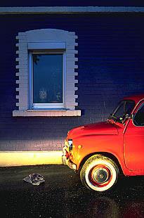 Roter Fiat 500 vor blauer Hauswand