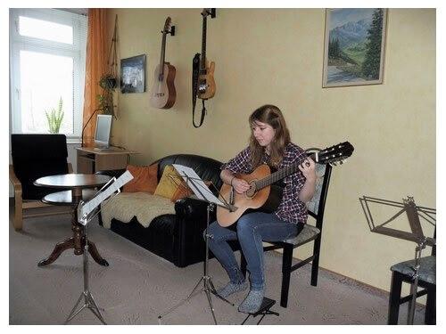 Gitarrenschülerin hat Spass beim Gitarre spielen