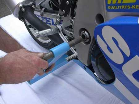 Zur rechten Seite der Maschine wechseln, den Ständer anheben, den Bolzen durch die Buchse in oder auf die Schwingenaufnahme schieben / Now change to the right side and push the fitting, then push the bolt through the bush.