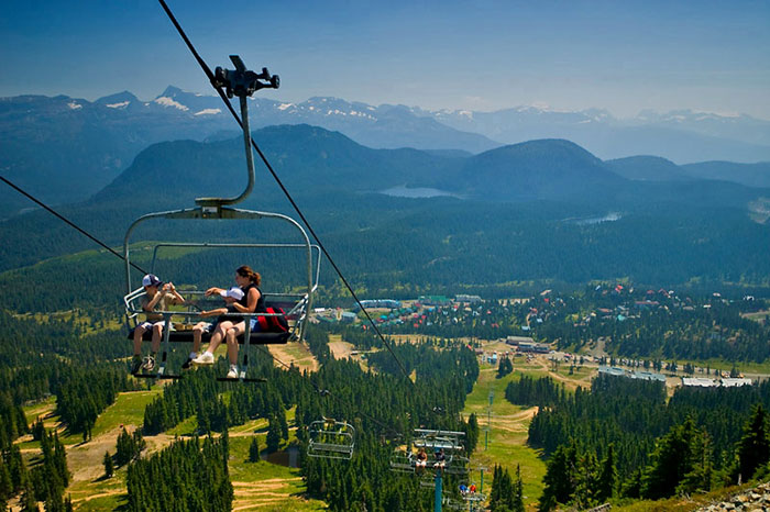 A woman and two children ride a chairlift on Mount Washington in the summer.