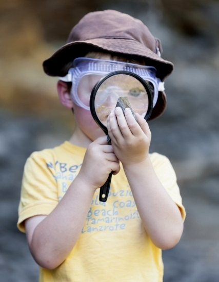 Young boy with magnifying glass looking at a fossil on the banks of the Puntledge River in Courtenay.