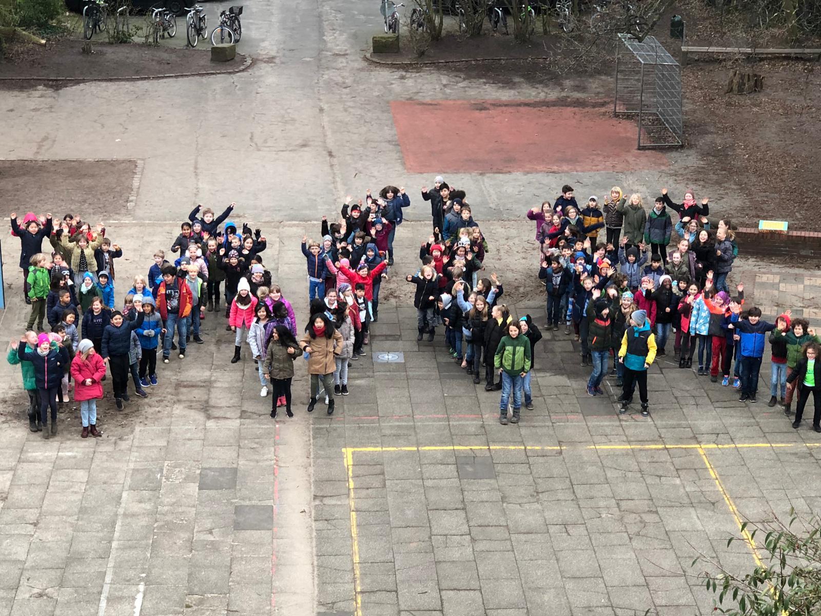 """Unser """"WIR"""" mit allen Klassen auf dem Schulhof"""