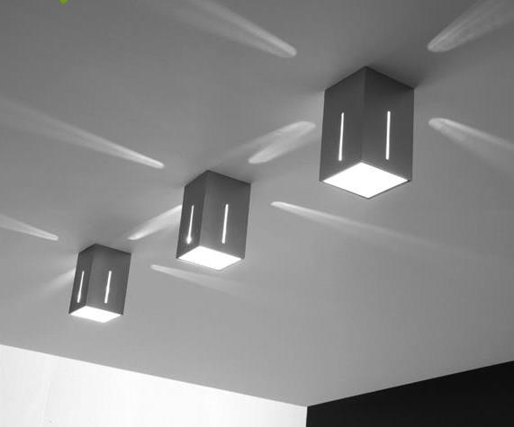 Faretto da soffitto in metallo dal design squadrato con copertura in vetro satinato saldato con il corpo in metallo verniciato bianco. Dona un'illuminazione diretta verso il basso, ma anche piacevoli effetti di luce attraverso le fessure laterali.