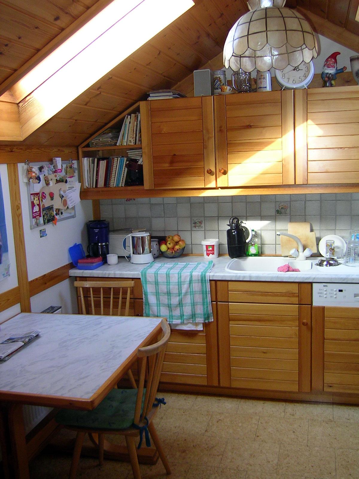 Küche in Dachgeschoss eingepasst, mit eleganter Front in massivem Kiefernholz