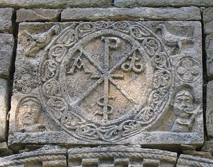 Spätantike Darstellung des Chritogramms Chi-Rho an der Kirche Santa Maria de l'Assumpció in Cóll (Spanien).