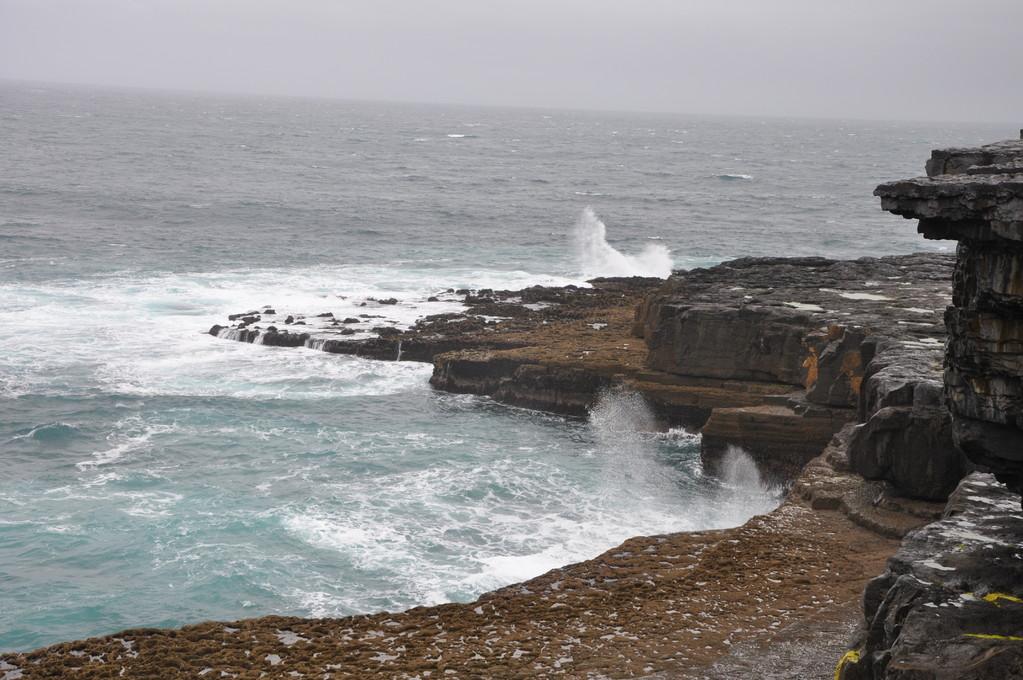 Les vagues se fracassent contre la falaise.