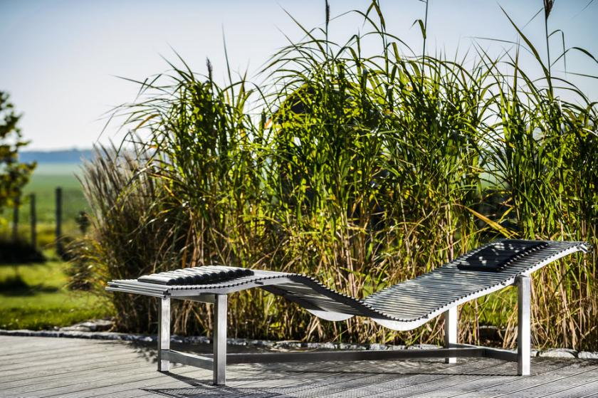 Dimaro Edelstahl Sonnenliege Solem auf Holzterrasse vor grünem Schilfgras