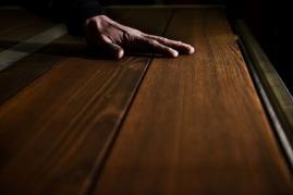 Hand streicht über Eschenholz Oberfläche Manufaktur